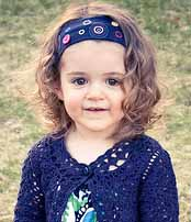 Girl with dark curly hair and head band