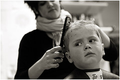 Child getting a haircut by a hairdresser in a salon