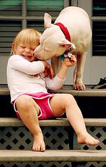 A girl being licked by a dog