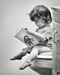 Girl reading on a toilet