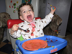 Messy toddler feeding himself in a high chair