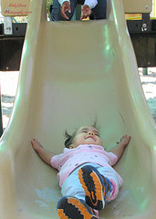 Parent letting a child go down the slide
