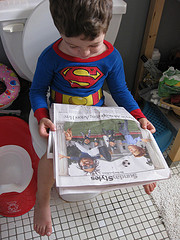 Reading newspaper on a toilet