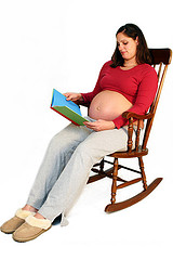 Pregnant woman reading in a rocking chair