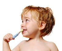 A toddler brushing his teeth with a toothbrush