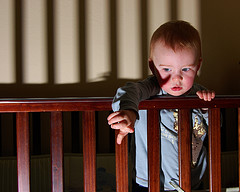A toddler alone in a crib with shadows
