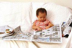 Toddler girl reading a newspaper